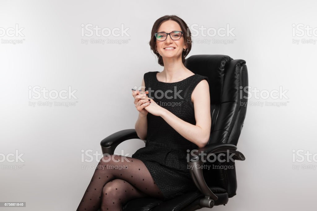 Picture of beautiful woman in black dress sitting in the armchair royalty-free stock photo