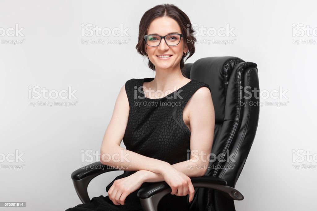 Picture of beautiful woman in black dress sitting on a armchair royalty-free stock photo