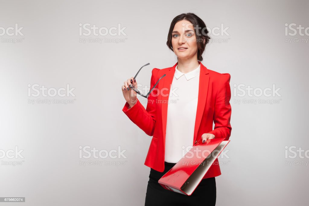 Picture of beautiful woman in red blazer standing with documents in hands royalty-free stock photo