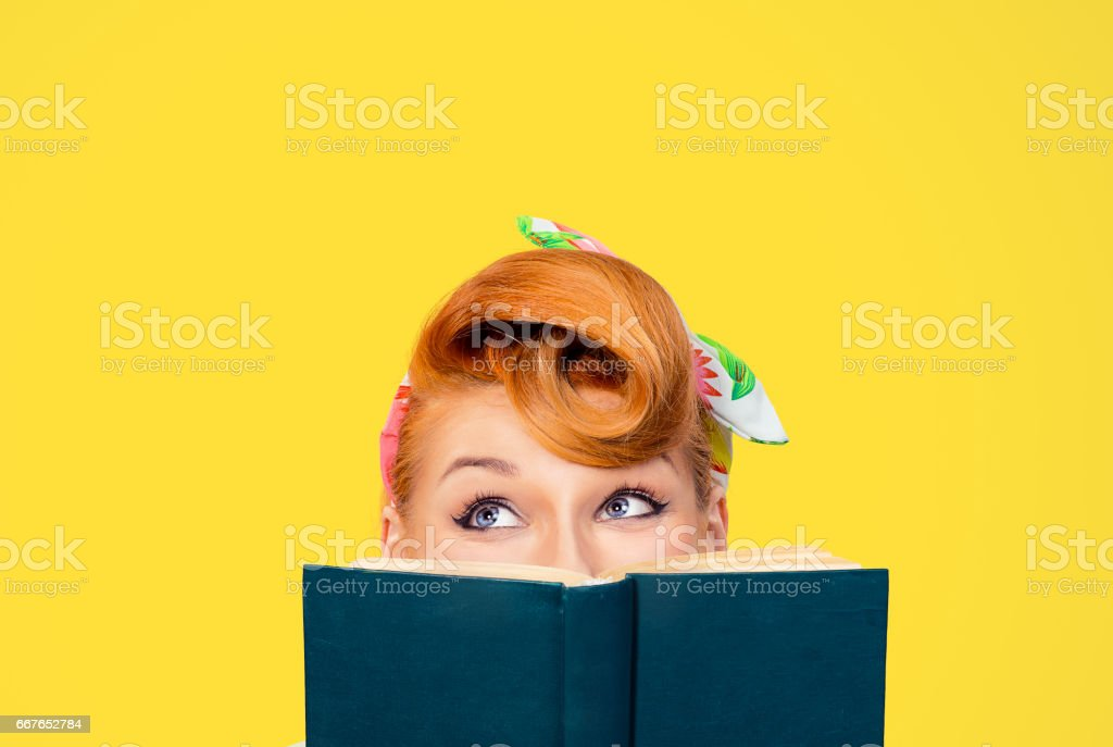 picture of cropped image close up head shot of pin up retro hair style woman holding green book looking up to copy space thinking isolated yellow background stock photo