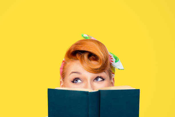 picture of cropped image close up head shot of pin up retro hair style woman holding green book looking up to copy space thinking isolated yellow background - pin up girl stock pictures, royalty-free photos & images
