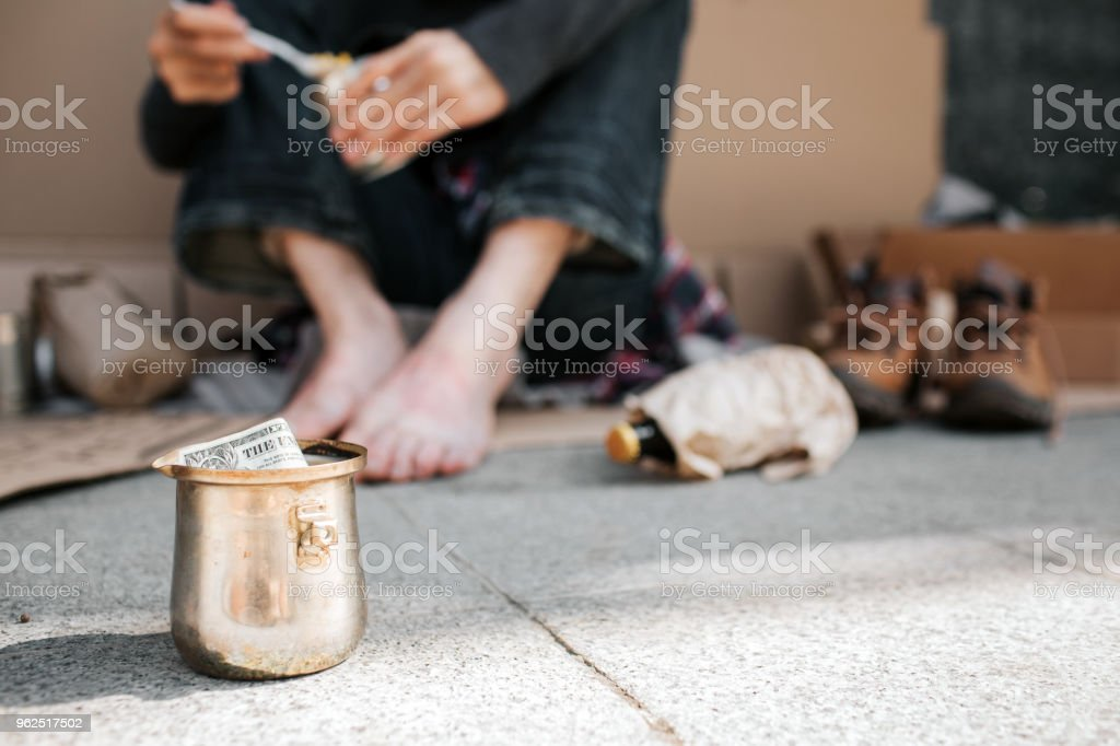 A picture of cup standing on concrete ground. There is a dollar in it. Also we can see beggar's legs. He is holding a can with food in hands and spoon as well. There are lots of things lying on ground - Royalty-free Adult Stock Photo