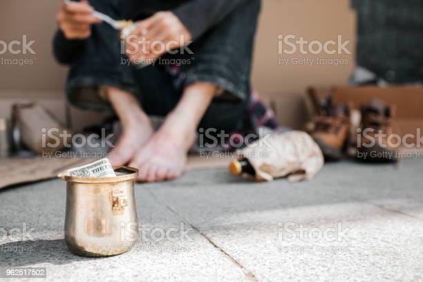 Foto de Uma Foto Da Taça De Pé No Chão De Concreto Há Um Dólar Nele Também Podemos Ver As Pernas Do Mendigo Ele Está Segurando Uma Lata Com Comida Nas Mãos E Colher Também Existem Muitas Coisas Deitado No Chão e mais fotos de stock de Adulto