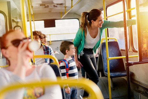 Picture of cute little boy in a bus. Holding his mothers hand and looking through the window.