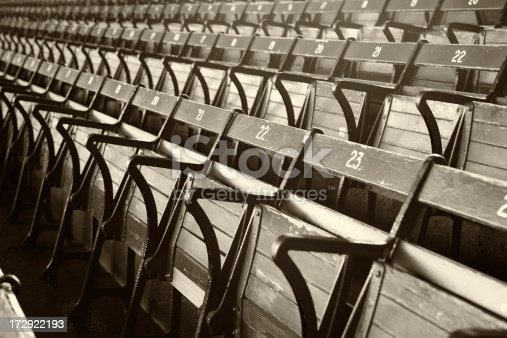 Old Time stadium seats in gray scale with a sepia tone. Shallow DOF focal point is the number