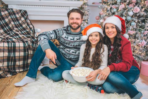 bild der familie stock sitzen und lächeln vor der kamera. junger mann hat die fernbedienung in der hand. mädchen hält schüssel popcorn. sie lehnt sich an mutter. - kinder weihnachtsfilme stock-fotos und bilder