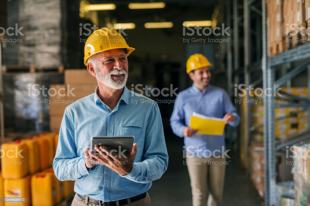 Picture of father and son walking through their warehouse with helmets on their heads. Father is holding digital tablet in his hand and looking at shelf full of boxes with smile on his face. stock photo