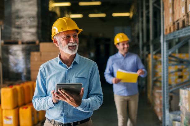 picture of father and son walking through their warehouse with helmets on their heads. father is holding digital tablet in his hand and looking at shelf full of boxes with smile on his face. - owner stock pictures, royalty-free photos & images