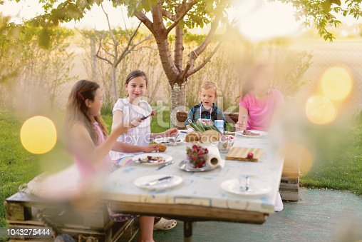istock Picture of four kids sitting by the table in nature and eating. Beautiful summer day. 1043275444