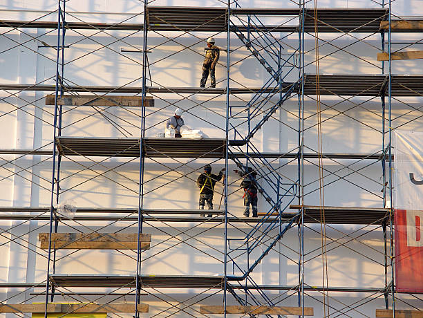 Picture of four men working on a scaffolding  Photo of Construction Workers on Scaffolding. scaffolding stock pictures, royalty-free photos & images