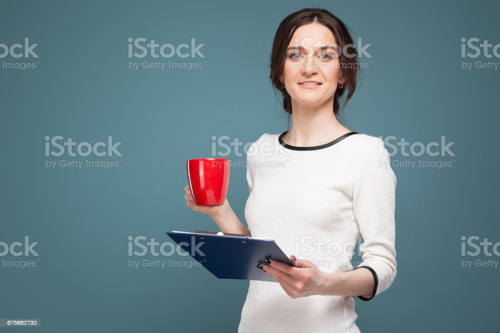 Picture of good looking woman in light clothes standing with coffe and recordings in hands royalty-free stock photo