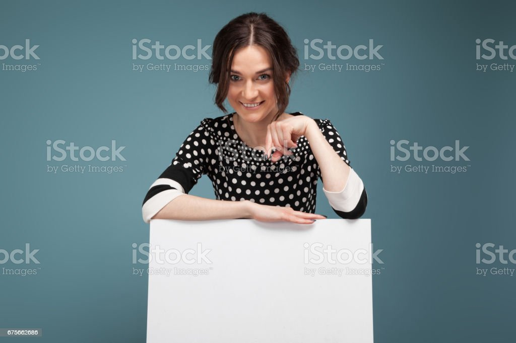 Picture of good looking woman in speckled clothes standing with big paper in hands royalty-free stock photo