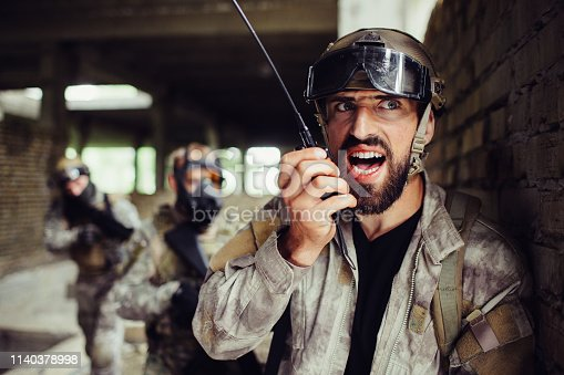 istock A picture of guy standing and leaning to wall. He is talking to a portable radio. His fighters are standing behind him and ready to attack in any time. They have rifles in hands. 1140378998