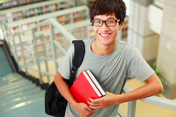 picture of happy college student in the library stock photo