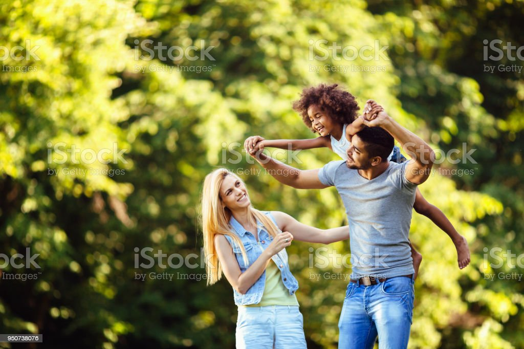 Picture of happy young couple spending time with their daughter stock photo