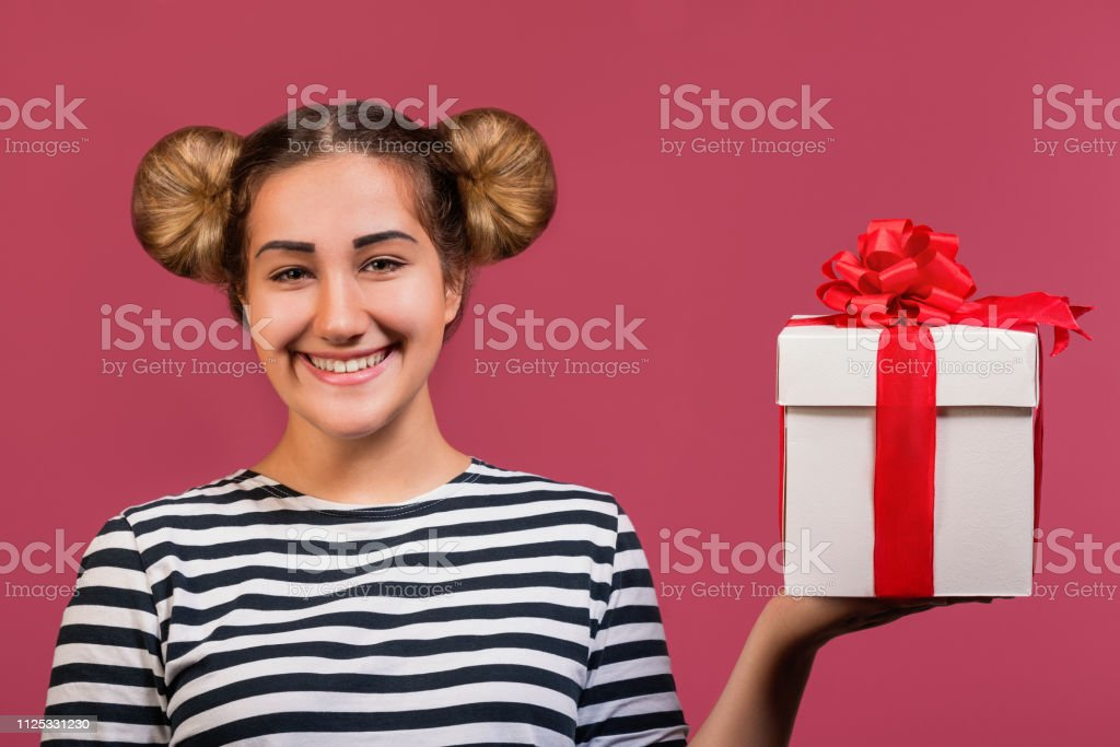 Picture of hipster girl with funny hairstyle holding the gift box on...