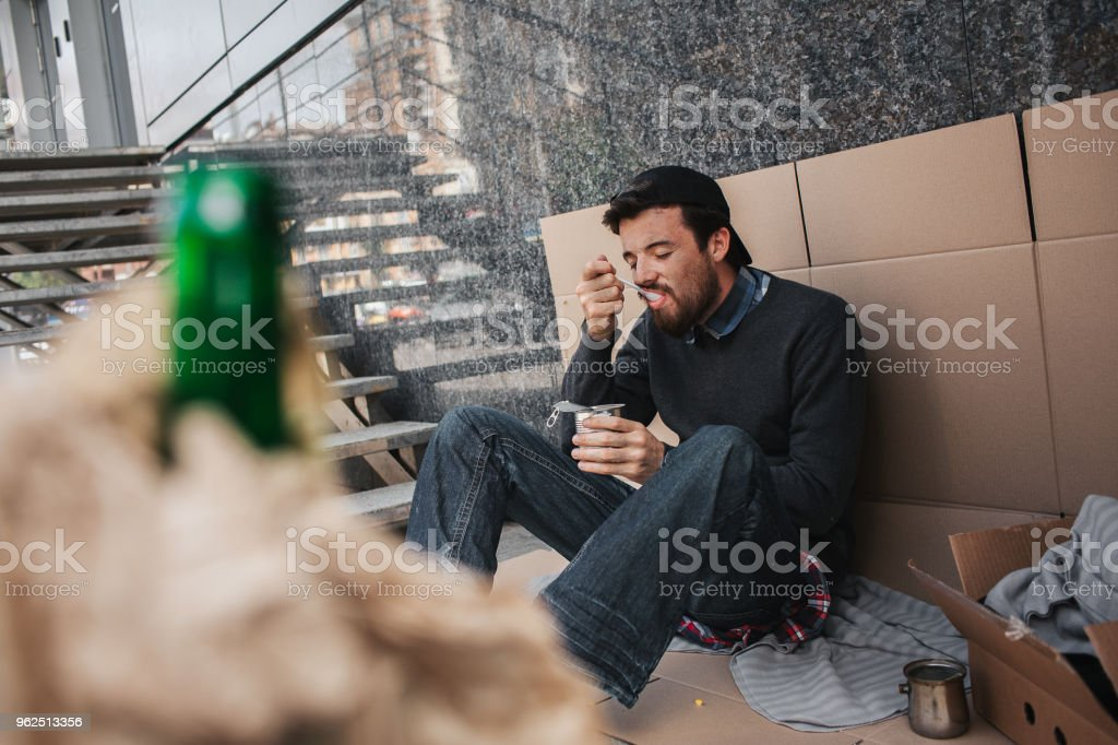 A picture of homeless man sitting on cardboard and eating food from can. Also there is a green bottle in brown paper in front of picture. Man is devouring food - Royalty-free Adult Stock Photo