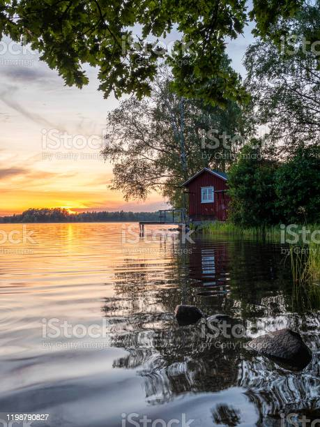 Photo of Picture of Lakeside Sunset with trees, scandinavian wooden house and blue sky