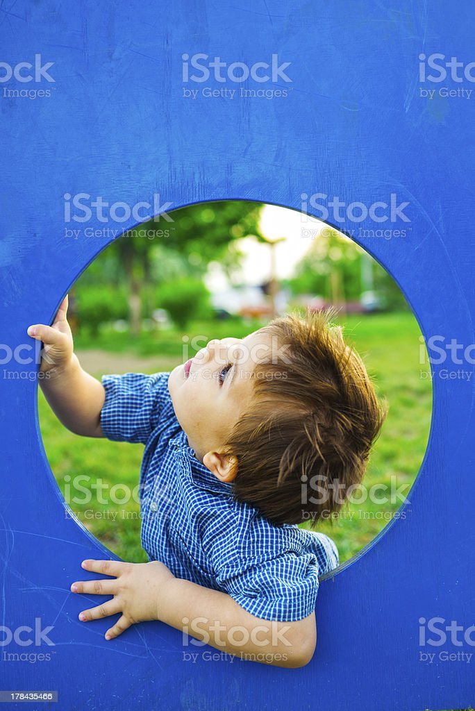 Picture of little boy exploring blue climbing gym stock photo