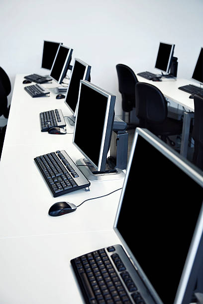 A picture of long, white desks with black computers. stock photo