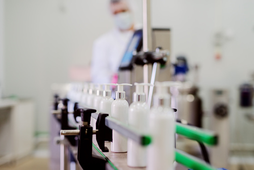 Picture of lotion bottles on production line. Bottles of cosmetic products in factory production line.