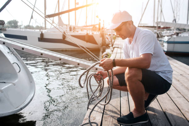 Picture of man in white cap and shirt sitting in squad position on pier. He holds lots of ropes. Guy is calm and peaceful. He is concentrated. Picture of man in white cap and shirt sitting in squad position on pier. He holds lots of ropes. Guy is calm and peaceful. He is concentrated mooring stock pictures, royalty-free photos & images