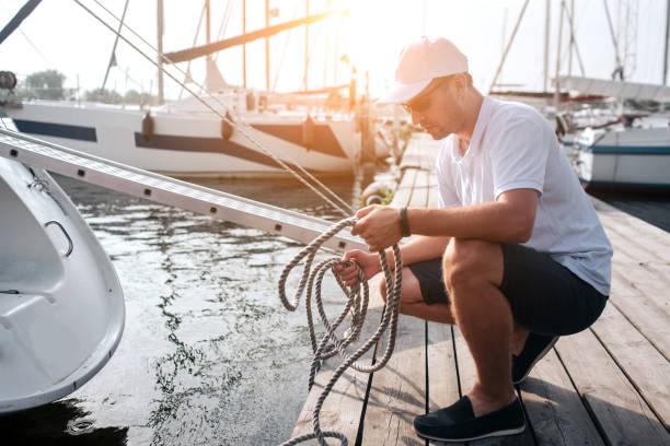 foto van man in white cap en shirt zittend in squad positie op de pier. hij heeft veel touwen. guy is rustig en vredig. hij is geconcentreerd. - aangemeerd stockfoto's en -beelden