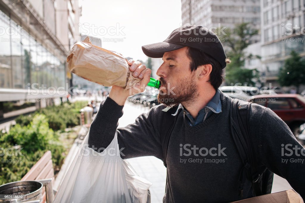 A picture of man standing on the street and drinking from bottle. He is homeless. Guy has a bag hanging on his hand and a box with different stuff - Royalty-free Adult Stock Photo