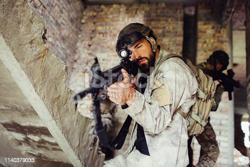istock A picture of man taking aim through rifle's lenz. He is looking straight forward. Guy is serious and concentrated. Other two guys are standing behind him. 1140379033