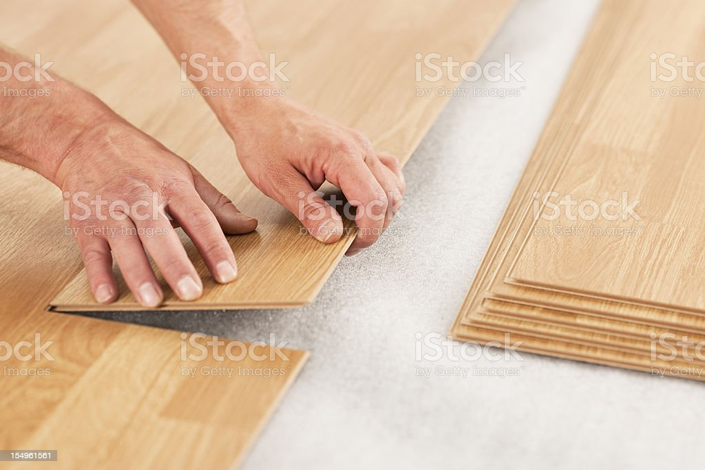 Picture of man's hands laying yellow laminate flooring stock photo