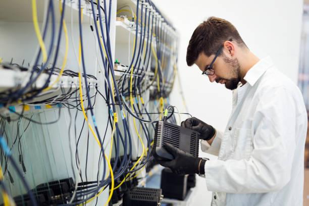 picture of network technician testing modems in factory - człowiek maszyna zdjęcia i obrazy z banku zdjęć