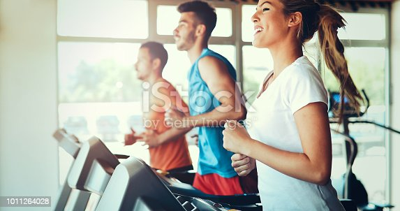 879180126istockphoto Picture of people running on treadmill in gym 1011264028