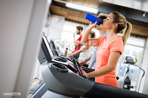 879180126istockphoto Picture of people running on treadmill in gym 1055027176