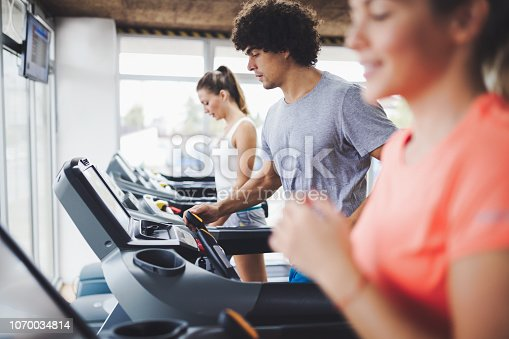 879180126istockphoto Picture of people running on treadmill in gym 1070034814