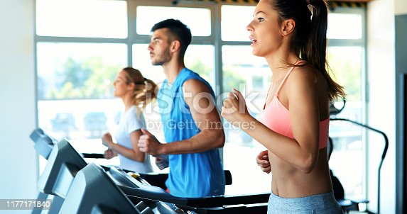 879180126istockphoto Picture of people running on treadmill in gym 1177171840