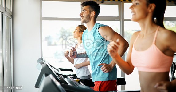 879180126istockphoto Picture of people running on treadmill in gym 1177171850