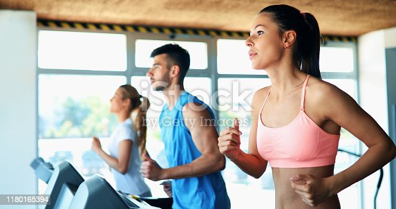 879180126istockphoto Picture of people running on treadmill in gym 1180165394