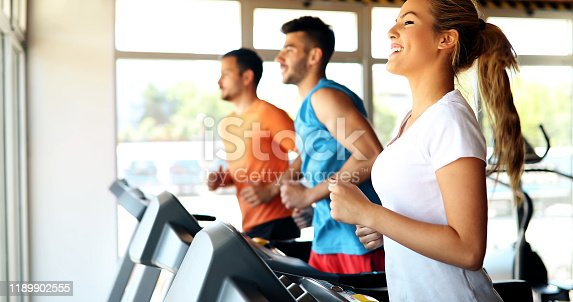 879180126istockphoto Picture of people running on treadmill in gym 1189902555