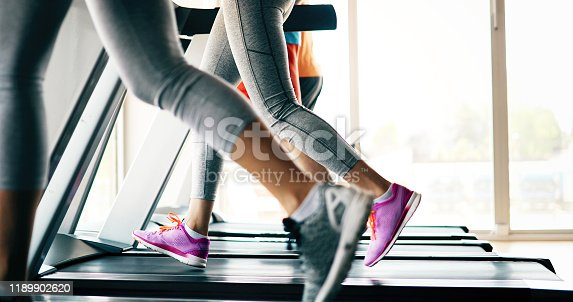 879180126istockphoto Picture of people running on treadmill in gym 1189902620