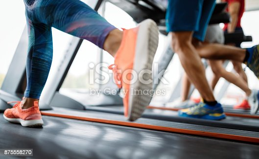 879180126istockphoto Picture of people running on treadmill in gym 875558270