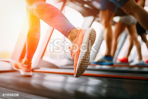 879180126istockphoto Picture of people running on treadmill in gym 875558336