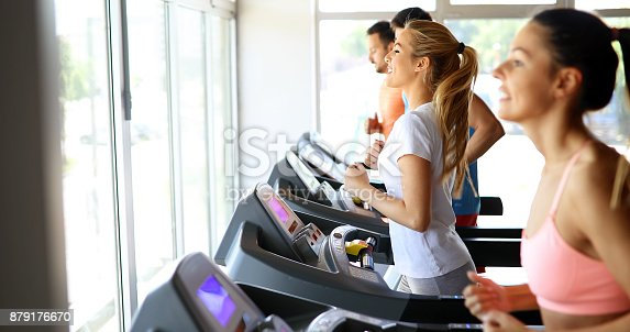 879180126istockphoto Picture of people running on treadmill in gym 879176670