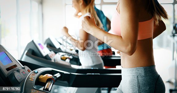 879180126istockphoto Picture of people running on treadmill in gym 879176780