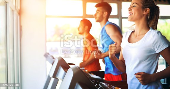 879180126istockphoto Picture of people running on treadmill in gym 879177246