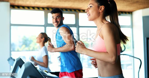879180126istockphoto Picture of people running on treadmill in gym 879177422