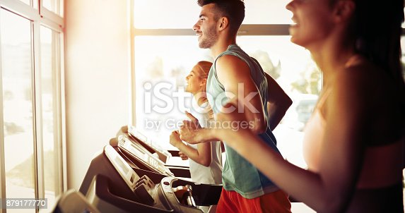 879180126istockphoto Picture of people running on treadmill in gym 879177770