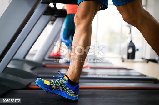 879180126istockphoto Picture of people running on treadmill in gym 908982172