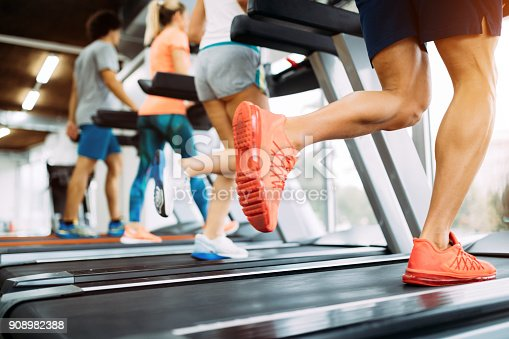 879180126istockphoto Picture of people running on treadmill in gym 908982388