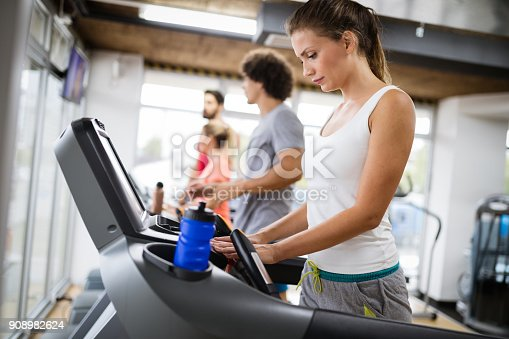 879180126istockphoto Picture of people running on treadmill in gym 908982624