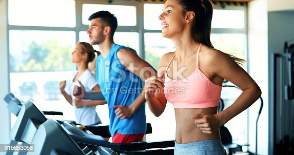 879180126istockphoto Picture of people running on treadmill in gym 915653058
